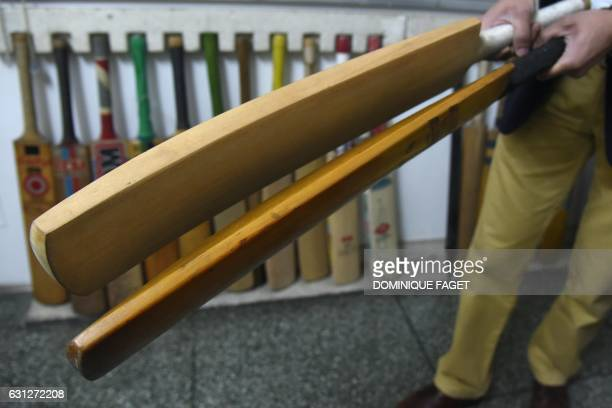 In this photograph taken on December 14 an Indian man holds old and new cricket bats in a factory in Meerut some 70kms northeast of New Delhi As...