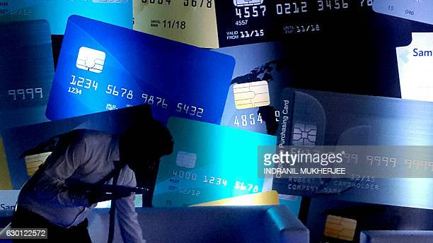 In this photograph taken on December 16 an Indian waiter makes his way past financially themed decorative panels at a function in Mumbai following...