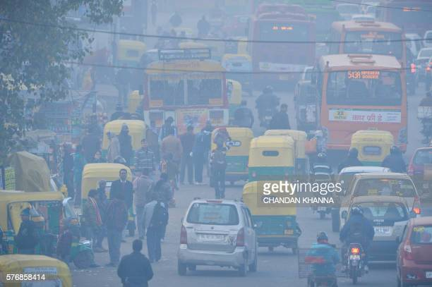 In this photograph taken on December 18 Indian commuters travel on a polluted road near a bus terminus in the Anand Vihar District of New Delhi An...
