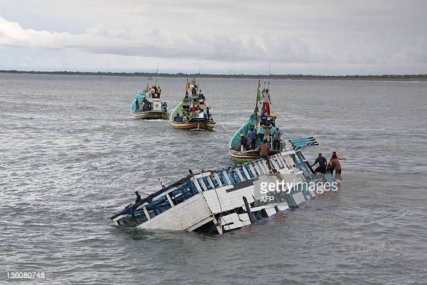 In this photograph taken on December 21 2011 rescuers check the wreckage of a people smuggler's boat seen half submerged after being towed near the...