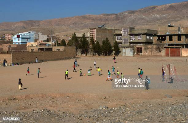 In this photograph taken on December 21 2017 Afghan youths play on a football pitch in Herat / AFP PHOTO / HOSHANG HASHIMI