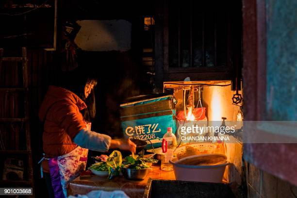 In this photograph taken on December 26 a woman prepares dinner in her home in Laoximen the city's oldest neighbourhood in Shanghai Amidst the...