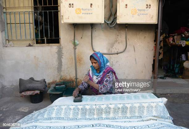 In this photograph taken on December 26 Indian worker Hasina Sadrawala prints a 'Abu Satara Shawl' using a hand held block at her home in Ahmedabad...