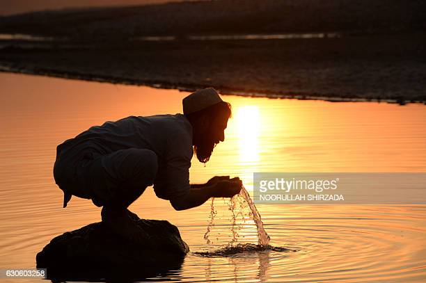 TOPSHOT In this photograph taken on December 27 an Afghan man performs ablution before prayers in a river on the outskirts of Jalalabad / AFP /...