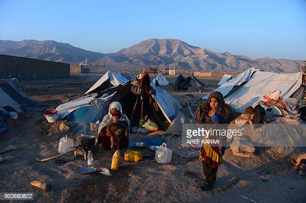 In this photograph taken on December 27 an internallydisplaced Afghan woman holds a child as she sits in front of her tent at refugee camp on the...