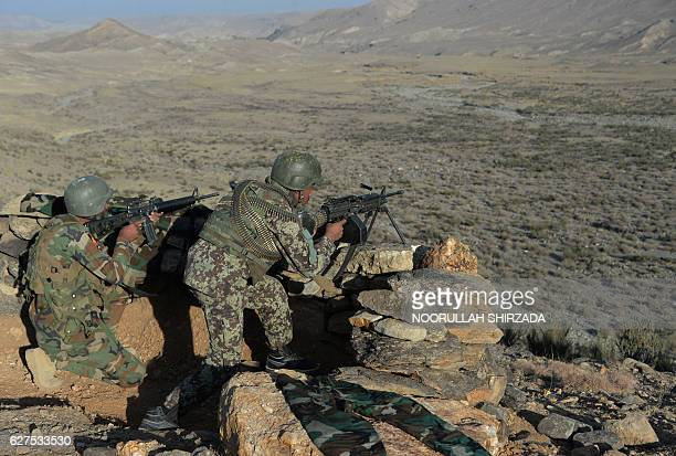 In this photograph taken on December 3 Afghan security forces take positions following an operation against Islamic State militants in Pachir Wa Agam...