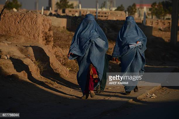 In this photograph taken on December 4 2016 shows two burqaclad Afghan women walking in the the old part of Herat / AFP / AREF KARIMI