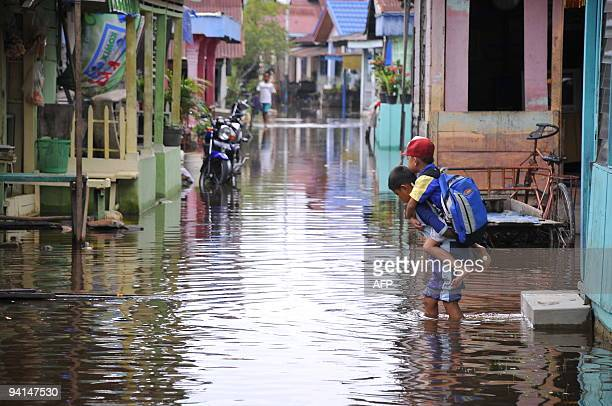 In this photograph taken on December 7, 2009 Indonesian school children walk in a flooded street in Pekanbaru city in the Indonesian province of Riau...