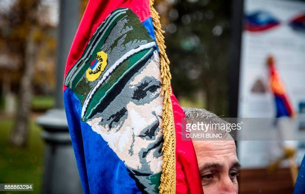 In this photograph taken on December 9 a Serbian nationalist holds a flag with an image of Bosnian Serb convicted war criminal Ratko Mladic as he...