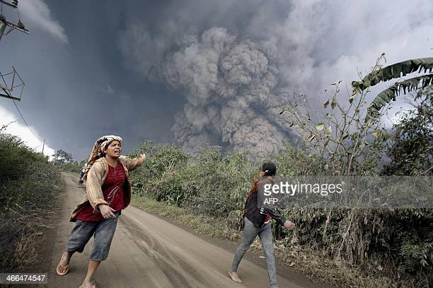 In this photograph taken on February 1 2014 residents run away to escape from hot volcanic ash clouds engulfing villages in Karo district during the...