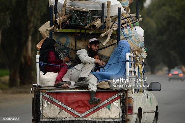 In this photograph taken on February 10 an internally displaced Afghan family rides on the back of a vehicle with their belongings as they flee from...