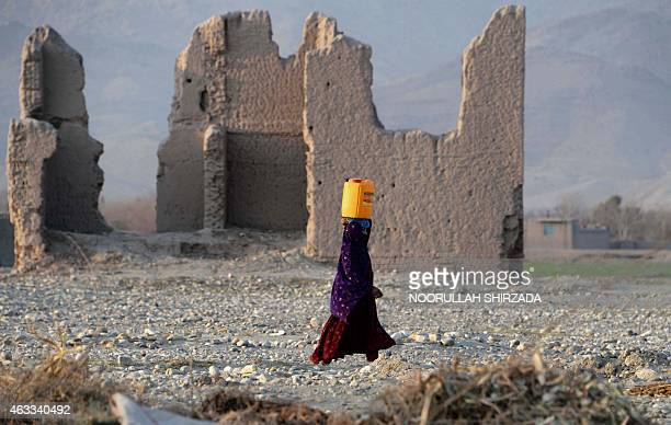 In this photograph taken on February 12 an Afghan Kuchi resident carries a water canister past ruins of a building destroyed during the AfghanSoviet...
