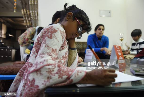 In this photograph taken on February 13 an Indian girl writes with traditional physical tools after working with a smartphone app created by Planet...