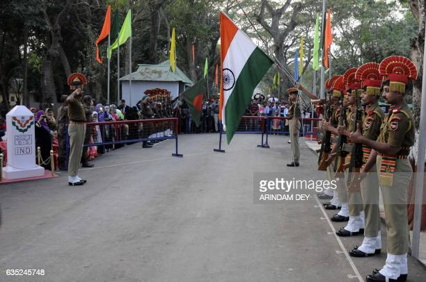 In this photograph taken on February 14 Indian Border Security Force personnel lower the tricolour flag during the Beating Retreat ceremony on the...