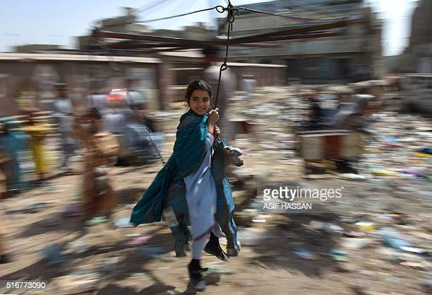 TOPSHOT In this photograph taken on February 18 Pakistani children ride on swings in the predominantly Pashtun Korangi District of Karachi In a...