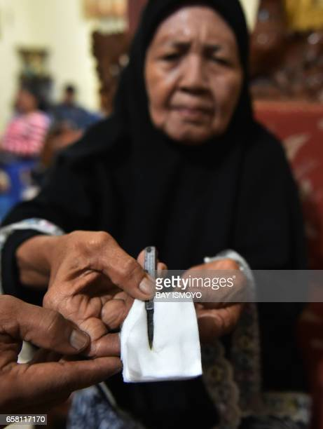 In this photograph taken on February 20 a traditional healer shows cutting tools used to circumcise women in Gorontalo in Indonesia's Gorontalo...