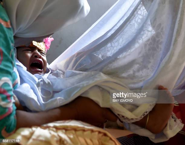 In this photograph taken on February 20 toddler Salsa Djafar cries as a traditional healer conducts a circumcision, in Gorontalo in Indonesia's...