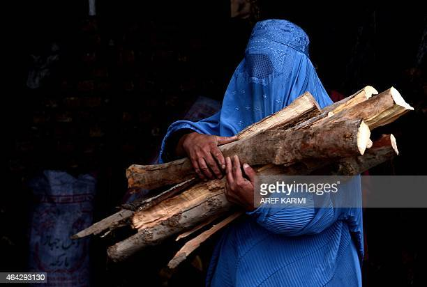 In this photograph taken on February 23 a burqaclad Afghan woman carries chopped logs after buying them at a firewood yard in Herat AFP PHOTO/AREF...