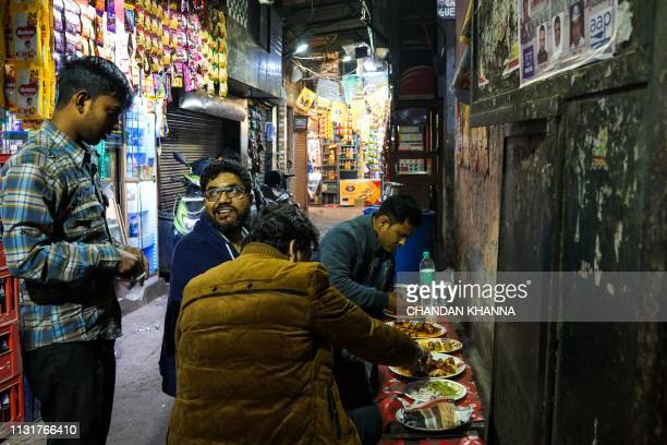 In this photograph taken on February 24 2019 Indian patrons eat at a roadside food stall in the old quarters of New Delhi For the wellheeled in New...