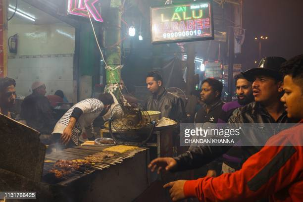 In this photograph taken on February 24 2019 Indian patrons wait to be served at a roadside food stall in the old quarters of New Delhi For the...