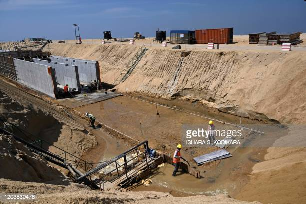 In this photograph taken on February 24, 2020 labourers work at a construction site on reclaimed land, part of a Chinese-funded project for Port...