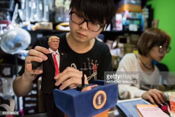 In this photograph taken on February 3 a member of staff adjusts the tie of a prototype figurine replica of US President Donald Trump made by...
