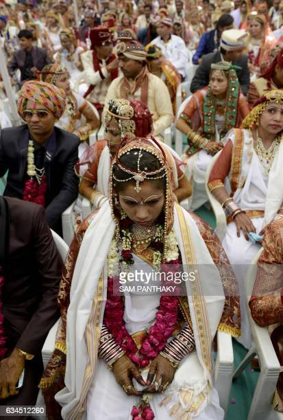 In this photograph taken on February 3 an Indian bride looks on as she participates with others in a mass wedding ceremony of the Thakore community...