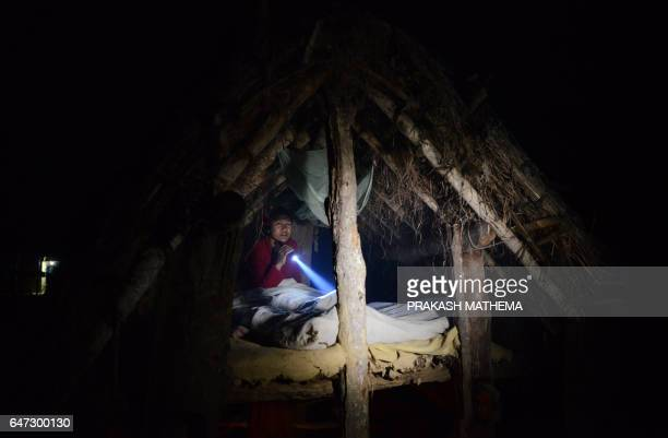 In this photograph taken on February 3 Nepalese woman Pabitra Giri prepares to sleep in a Chhaupadi hut during her menstruation period in Surkhet...