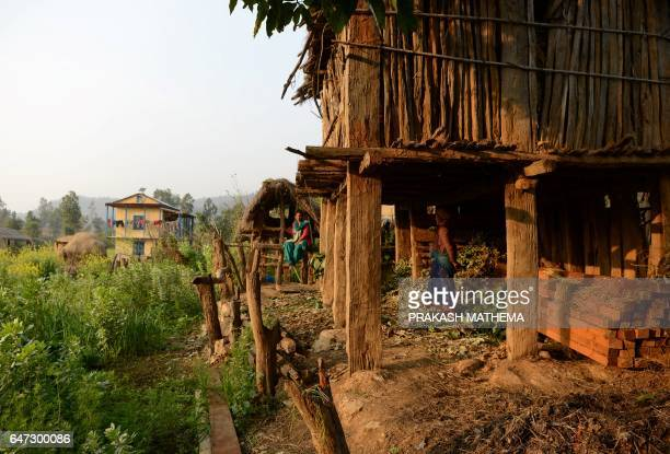 In this photograph taken on February 3 Nepalese woman Yum Kumari Giri looks at a Chhaupadi hut during her menstruation period in Surkhet District...
