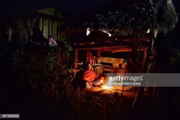 In this photograph taken on February 3 Nepalese women Pabitra Giri and Yum Kumari Giri sit by a fire as they live in a Chhaupadi hut during their...