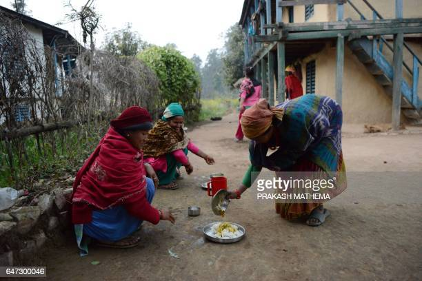 In this photograph taken on February 3 Nepalese women Pabitra Giri and Yum Kumari Giri prepare to have dinner outside their house during their...