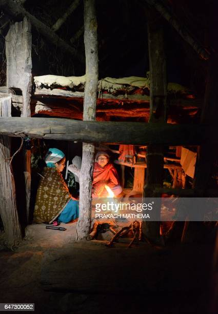 In this photograph taken on February 3 Nepalese women Pabitra Giri and Yum Kumari Giri keep warm by a fire as they live in a Chhaupadi hut during...