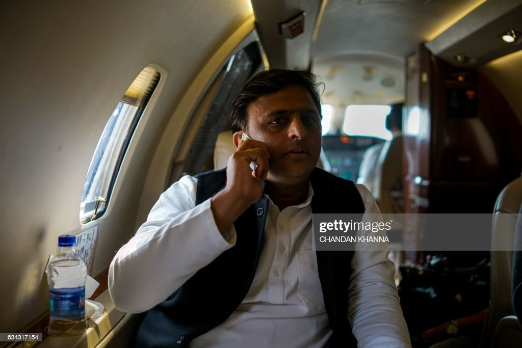 In this photograph taken on February 3 Uttar Pradesh state Chief Minister Akhilesh Yadav talks a telephone inside an aircraft as he flies between...