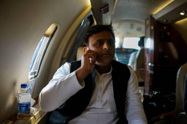 In this photograph taken on February 3 Uttar Pradesh state Chief Minister Akhilesh Yadav talks a telephone inside an aircraft as he flies between...