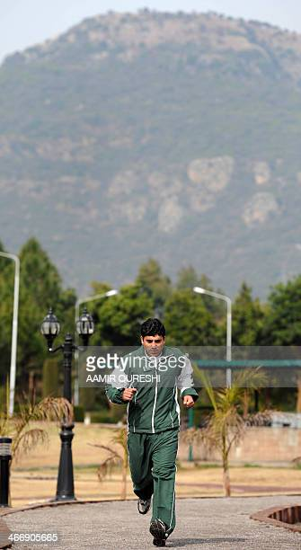 In this photograph taken on February 4, 2014 Pakistani skier Mohammad Karim runs during a training session in Islamabad. As a young boy, Mohammad...