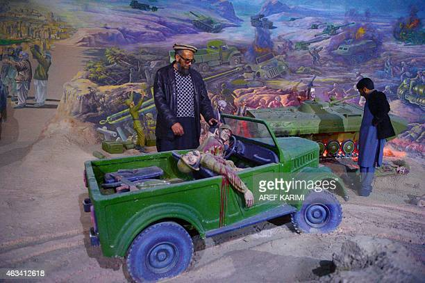 In this photograph taken on February 4 museum assistant and former Soviet soldier Sheikh Abdullah looks on at a display which depicts the Soviet...