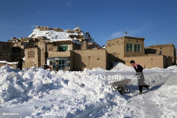 In this photograph taken on February 5 an Afghan man pushes a wheelbarrow following heavy snowfall in Ghazni province Heavy snowfall over the last...