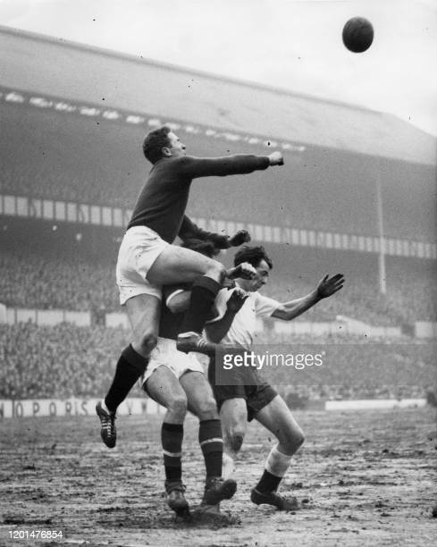 In this photograph taken on February 7 1959 Manchester United's Northern Ireland goalkeeper Harry Gregg punches the ball away over the heads of...