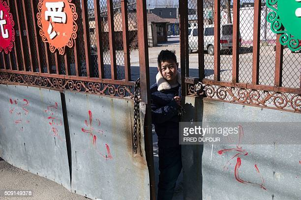 In this photograph taken on February 7 a child opens the main gate to an orphanage on the outskirts of Beijing the eve of the Lunar New Year While...