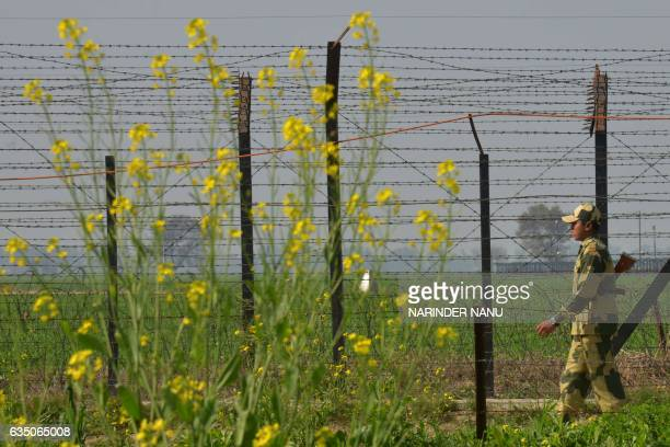 In this photograph taken on February 7 an Indian Border Security Force soldier walks alongside the IndiaPakistan border fence in Wagah some 45kms...
