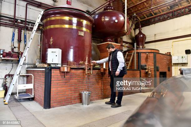 In this photograph taken on February 9 Frederic Barbot a producer of Cognac watches his alambic during the distillation process at Domaine...