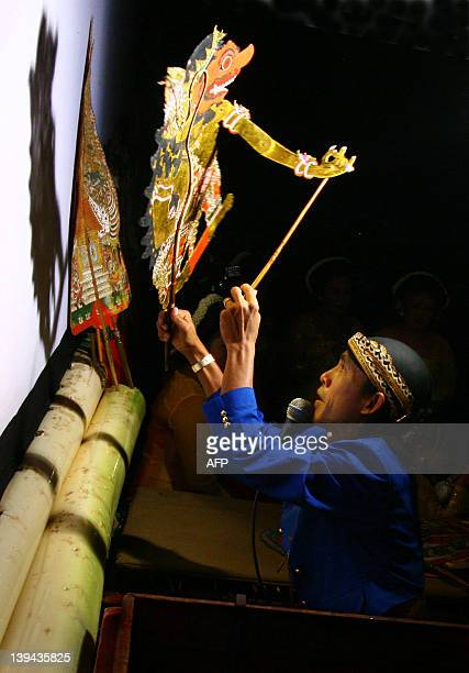 In this photograph taken on Februay 20 an Indonesian master puppeteer moves a Wayang Kulit puppet before a white screen during a cultural festival in...