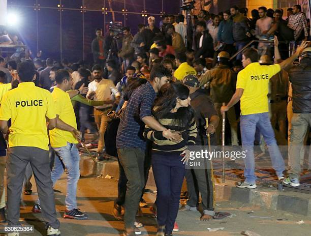 In this photograph taken on January 1 an Indian man helps a woman leave as police personnel try to manage crowds during New Year's Eve celebrations...