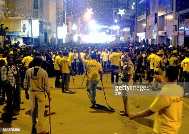 In this photograph taken on January 1 Indian police personnel holding 'lathi' sticks try to manage crowds during New Year's Eve celebrations in...