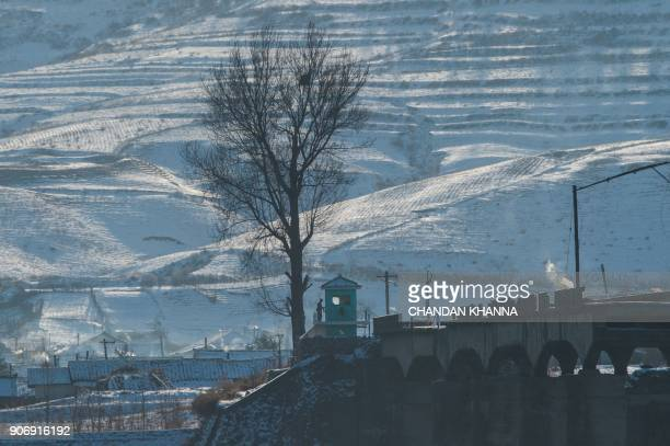 TOPSHOT In this photograph taken on January 10 2018 a North Korean soldier stands outside a guard post on the bank of the Yalu river near the North...
