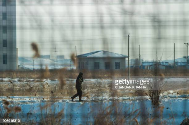 In this photograph taken on January 10 2018 a North Korean soldier walks along a dirt road in the North Korean town of Sinuiju opposite the Chinese...