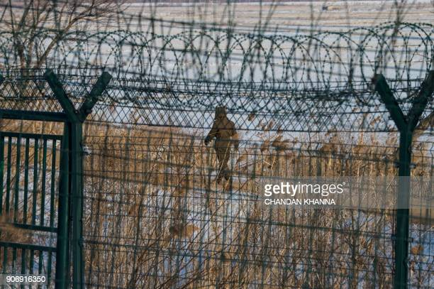 In this photograph taken on January 10 2018 a North Korean soldier walks along the border fence of North Korean town of Sinuiju opposite the Chinese...