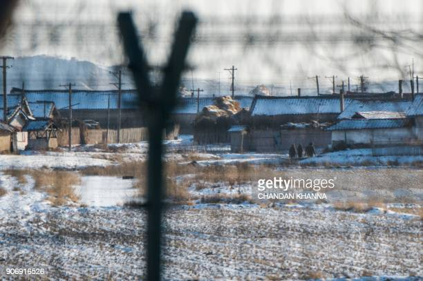In this photograph taken on January 10 2018 North Korean soldiers walk in the North Korean town of Sinuiju opposite the Chinese border city of...