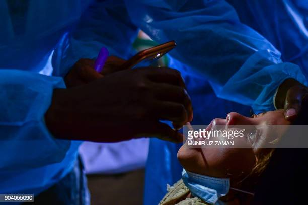 In this photograph taken on January 10 doctors from Médecins Sans Frontières examine Rohingya Muslim refugee Mohammad Rashed and who is infected with...