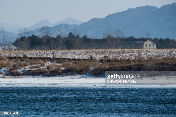 In this photograph taken on January 11 2018 a North Korean soldier walks along the banks of the Yalu river in the North Korean town of Sinuiju...